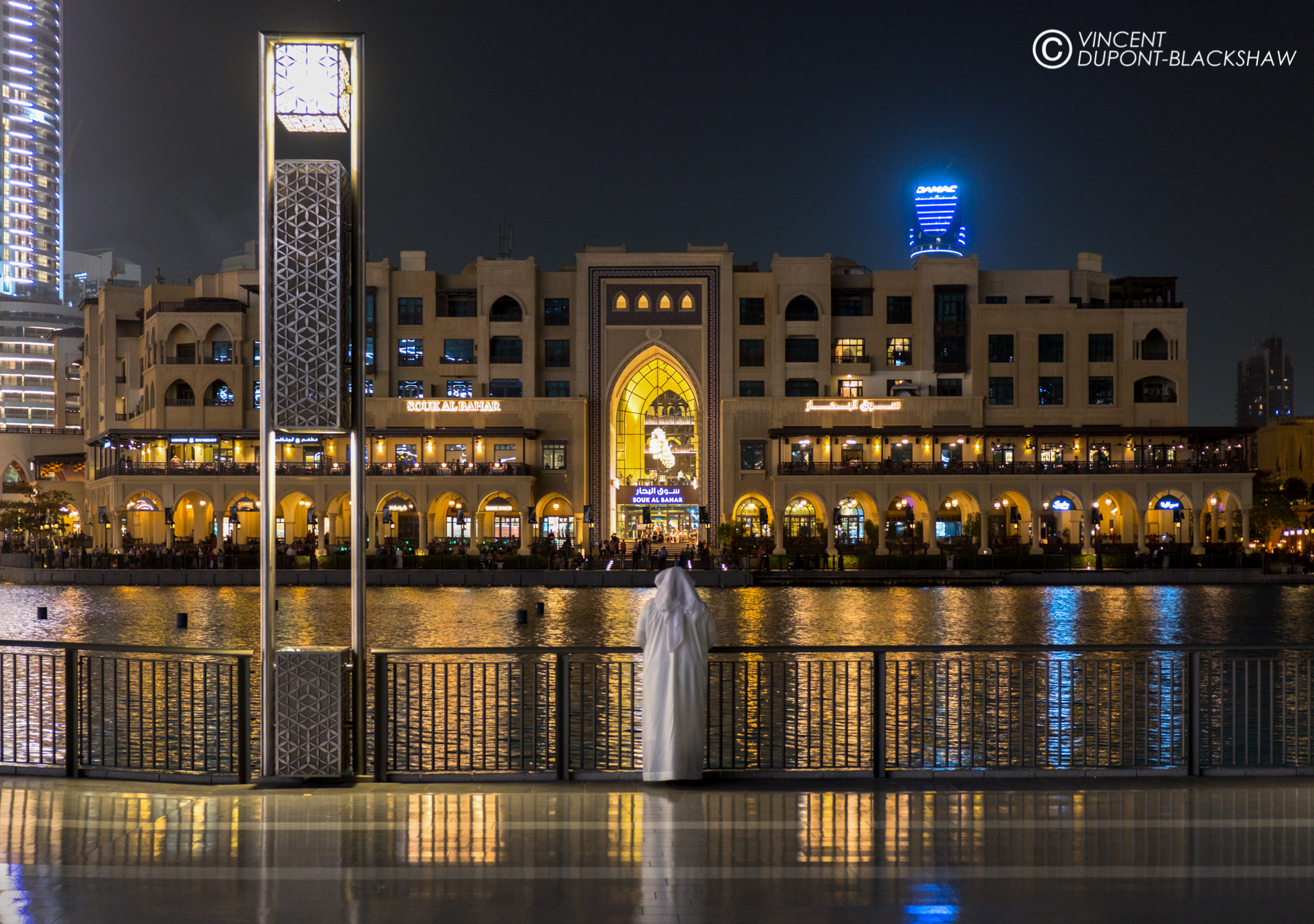 An emirati waits at the Dubai Fountain in the Dubai Mall